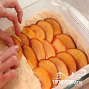 5.Пекарской  бумагой накрываем дно формы для выпечки. Тесто укладываем в форму. Разрезаем персики пополам и на десять частей – каждую половинку. Сверху на пирог выкладываем персики, легонько вдавливая в тесто ломтики. Пирог присыпаем сахаром и для расстойки оставляем минут на тридцать. Температура 200 градусов,  выпекаем тридцать минут.