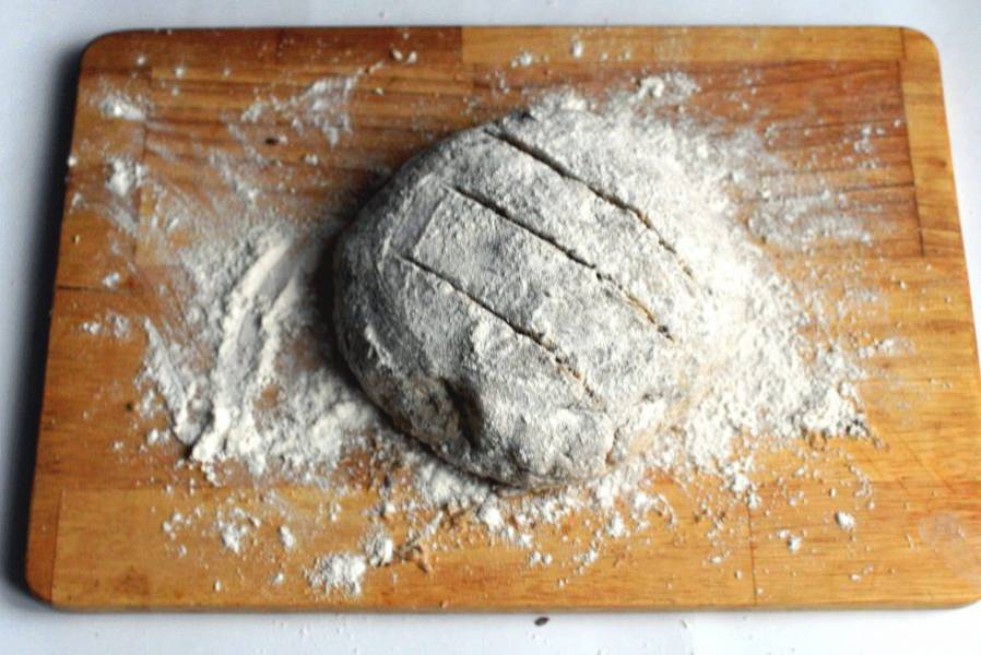 Руками, присыпанными мукой, сформуйте круглый хлеб, подворачивая края вниз. Присыпьте верх мукой и сделайте насечки. Тут же ставьте хлеб в прогретую до 200 градусов духовку минут на 25-30. Проверяйте готовность по цвету корочки и с помощью зубочистки.