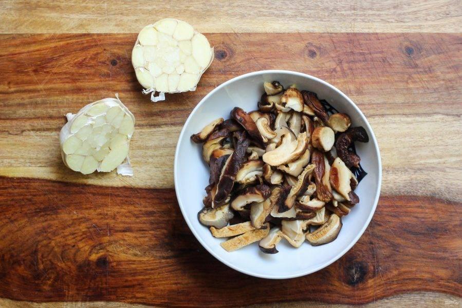 С чеснока снимите верхнюю шелуху и разрежьте целую головку поперек, грибы вымойте и нарежьте кусочками.