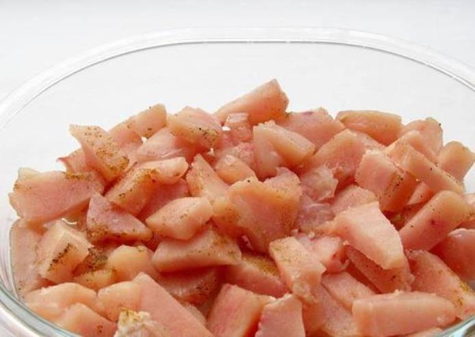 Форму для запекания смажьте растительным маслом. Выложите туда кусочки филе и посыпьте смесью  хмели-сунели и перцем.