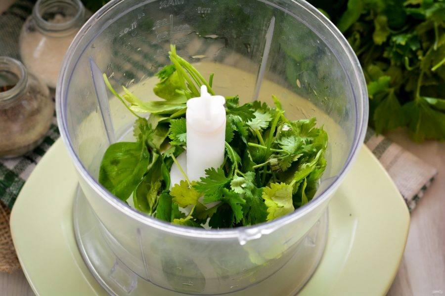 Зелень промойте, высушите и удалите жесткие веточки. В чашу блендера выложите листья зелени: базилика, кинзы и петрушки. Базилик можно использовать как фиолетовый, так и зеленый, на ваш выбор и вкус.