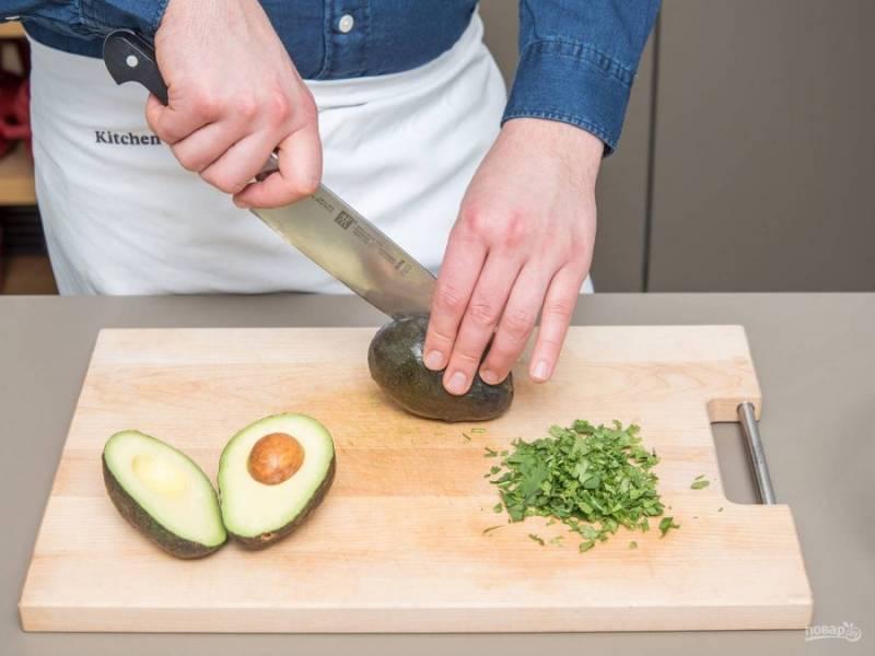 2. В это время авокадо нарежьте кубиками, а кинзу мелко нашинкуйте.