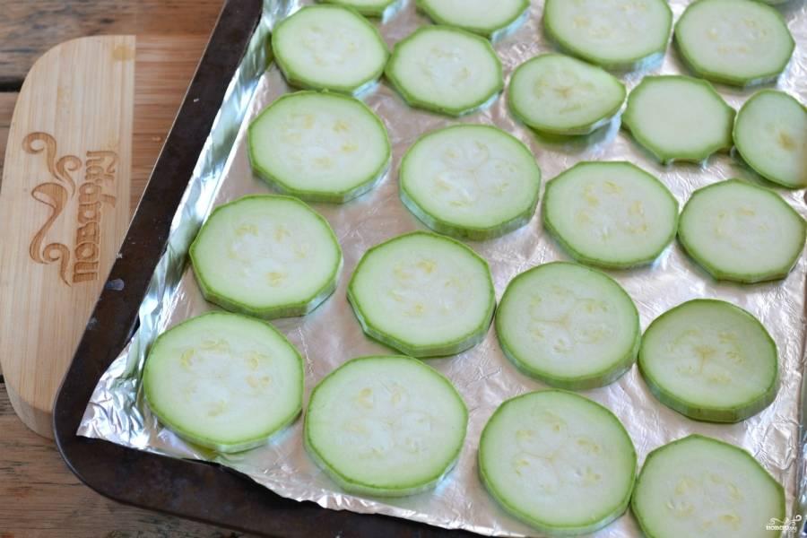 2.Противень смажьте растительным маслом. Кабачки порежьте кружочками толщиной около 5 мм. Выложите их на противень в один слой.