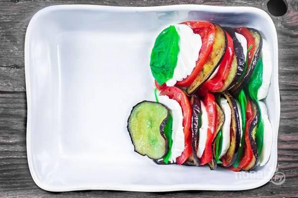 2.Вымойте листики базилика. Нарежьте моцареллу кружочками. Возьмите форму для запекания и уложите ингредиенты поочерёдно: сыр, базилик, баклажан, томат.