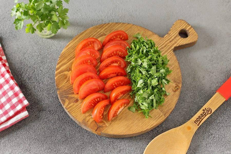 Помидоры нарежьте дольками, зелень порубите ножом. Когда суп будет готов, добавьте помидоры и зелень и через пару минут снимите с плиты. Дайте настояться под крышкой еще 15 минут.