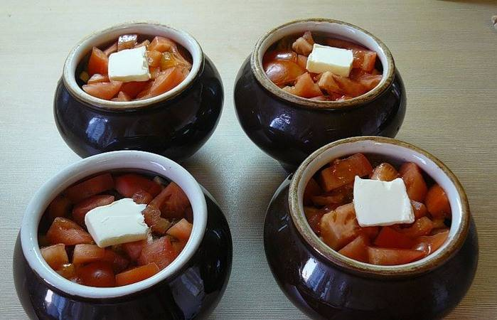 Затем идут баклажаны, после них разливаем по горшочкам приготовленную из помидоров и чеснока смесь, сверху делаем слой из помидоров, его также солим. Наливаем в каждый горшочек совсем немного водички и выкладываем сверху кусочек сливочного масла.