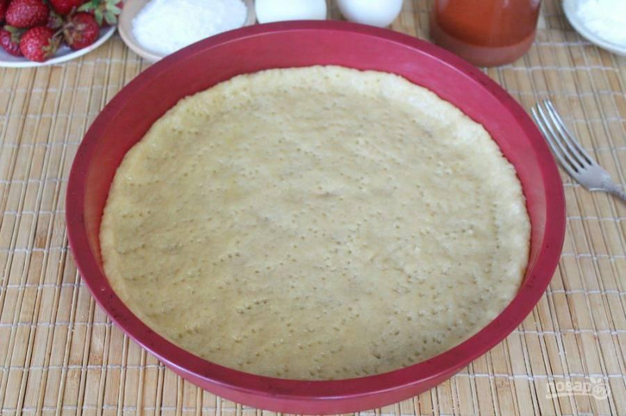 Далее, распределяем тесто по дну формы, оставляя по периметру бортик. Вилкой прокалываем по всей поверхности и отправляем в духовку на 15 минут. Запекаем при температуре 180-190 градусов, до легкого румяного оттенка.