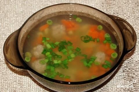 Накройте суп крышечкой и оставьте его томиться десять минут. Разлейте приготовленный суп по пиалам. Мелко нашинкуйте зеленый лук, добавьте по столовой ложке зелени в каждую тарелку.