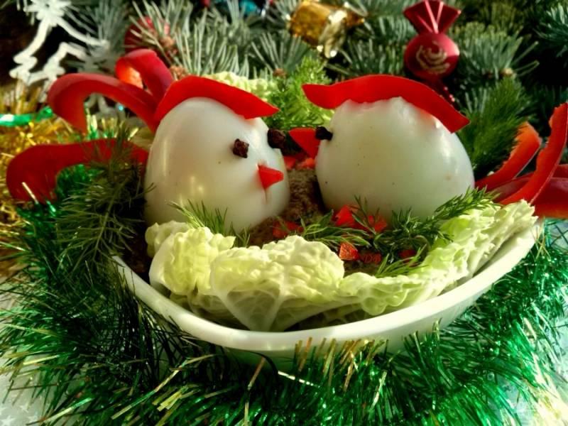 """Фаршированные яйца поставьте на паштет, сделайте надрезы для гребешка и клюва. Из болгарского перца нарежьте полоски для хвоста, клюва и гребешка, украсьте яйцо, имитируя петушка. Для глазок возьмите бутоны гвоздики.  """"Полянку"""" вокруг петушков украсьте зеленью и мелко нарезанным  сладким перцем. Приятного аппетита!"""