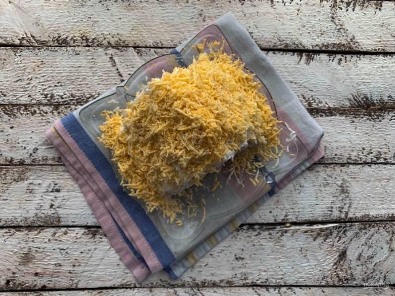Очистите яйца от скорлупы и разделите на белок и желток. Сначала выложите тертый яичный белок, затем желток. Именно для того, чтобы тертый белок хорошо держался на «крыше», салат необходимо слегка промазать сверху майонезом.