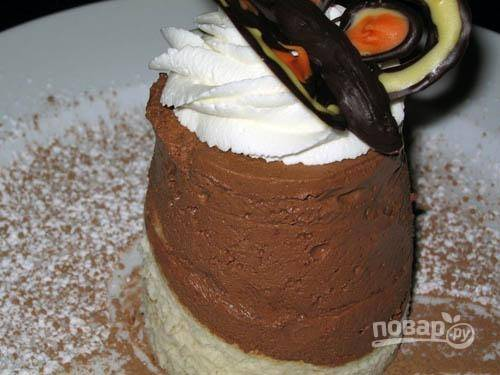 8. Когда десерт застынет, аккуратно достаньте его из формы и переверните белым шоколадом вниз, презентуя на тарелку. Поверх молочного шоколада оформите шапочку из взбитых сливок и установите шоколадную бабочку.