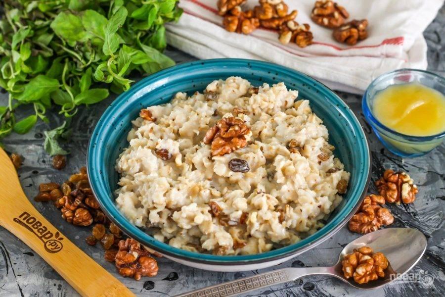 Выложите горячую геркулесовую кашу с грецкими орехами и изюмом в тарелки, подайте с медом теплой. Мед выкладывается только в остывшие до 35 градусов блюда, чтобы он не потерял своих полезных свойств.
