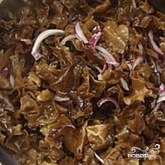2.Лук почистите и нарежьте полукольцами. В глубокой сковородке разогрейте масло и в течение 5-7 минут жарьте лук вместе с грибами.