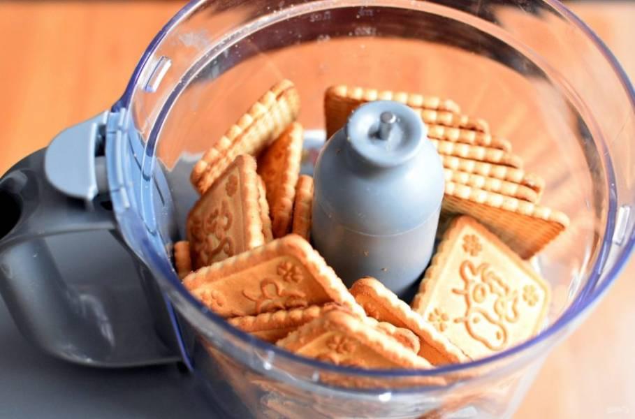 Поставьте духовку прогреваться до  температуры 180 градусов. Сахарное печенье пробейте в блендере в пульсовом режиме до очень  мелкой крошки.