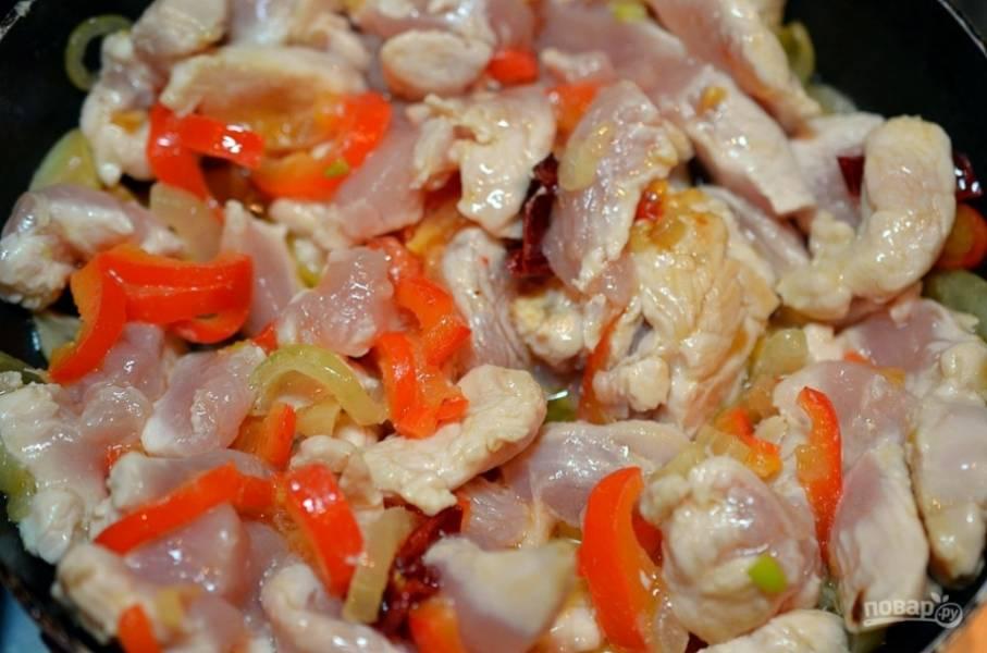Добавьте нарезанную на небольшие кусочки курицу, обжаривайте ещё минут 7.