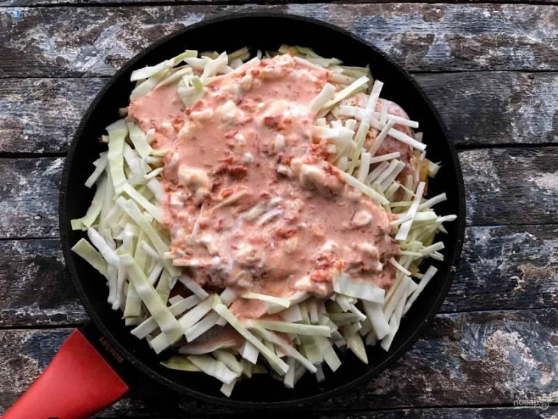 Выложите оставшуюся половину нарезанной капусты и залейте соусом из сметаны и томатного сока. Тушите все под закрытой крышкой 40 минут на медленном огне.