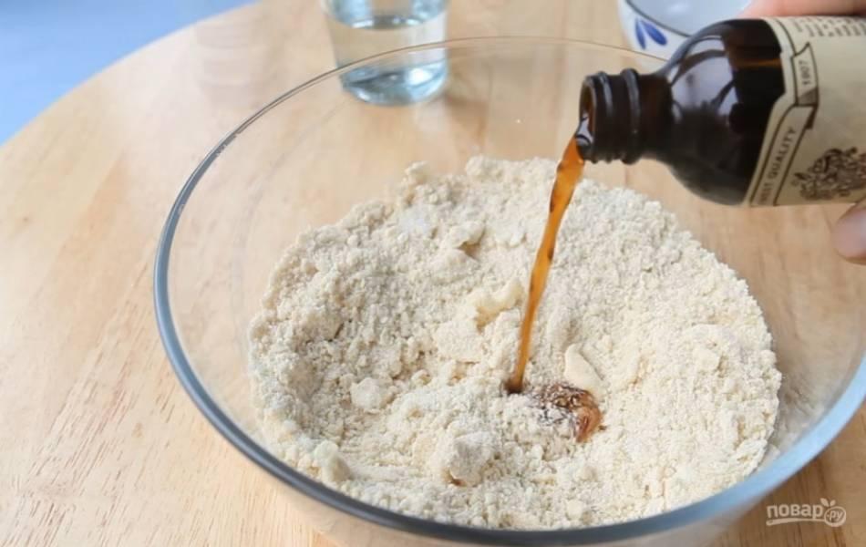 2.Высыпьте в миску муку и разотрите ее со сливочным маслом. Добавьте тертый миндаль, сахар, перемешайте. Добавьте ванилин, яичный желток и холодную воду.