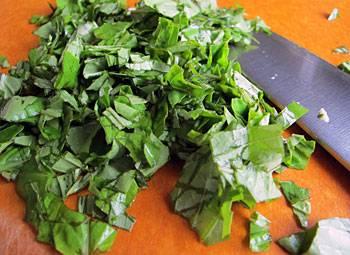3. Нарежьте зелень петрушки и базилик. Эти пряности великолепно дополнят вкус томатов и придадут блюду неповторимый аромат.