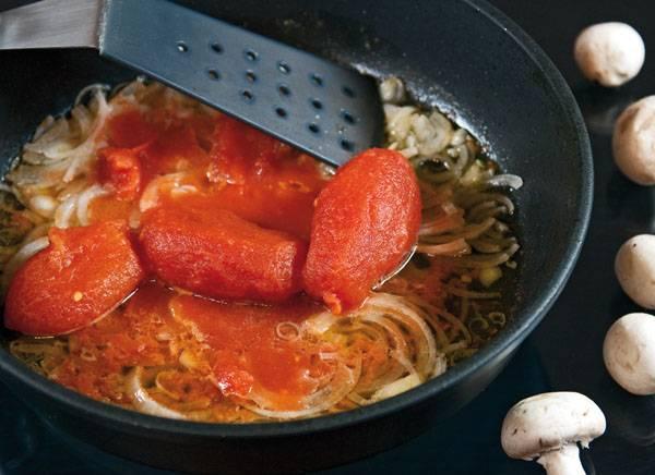2. Пока варится бульон, можно заняться овощами. На сковороде с небольшим количеством растительного масла обжарьте измельченный лук. Добавьте помидоры без кожицы (также можно использовать по рецепту приготовления солянки из кислой капусты томатную пасту или соус).