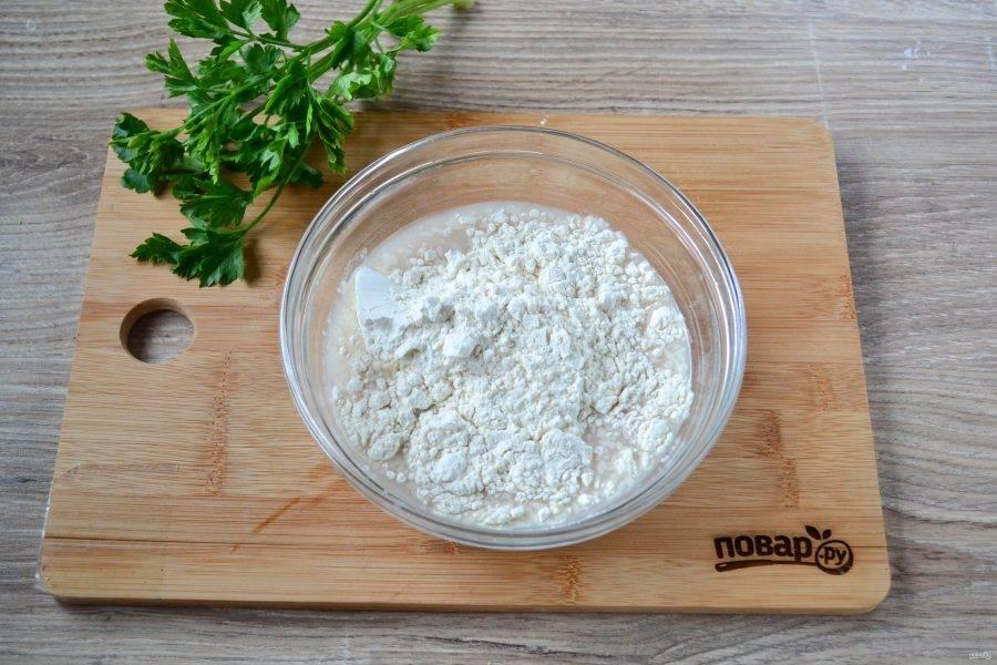 Влейте растительное масло, размешайте и начинайте вводить муку. Когда месить станет тяжело, переложите тесто на рабочую поверхность и замесите тесто руками. Тесто должно получиться мягким и нежным.