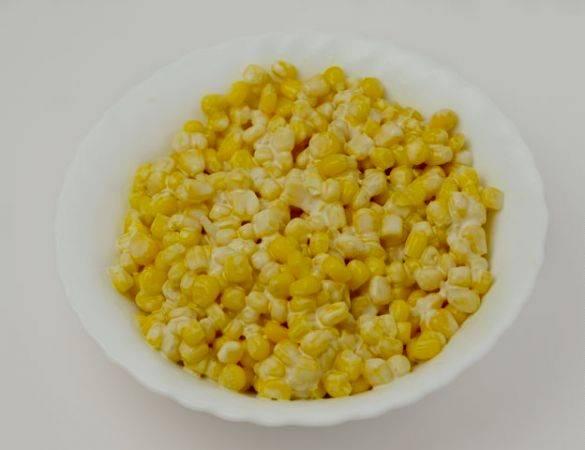 Сливаем жидкость с кукурузы, выкладываем ее в тарелку, добавляем майонез, перемешиваем.