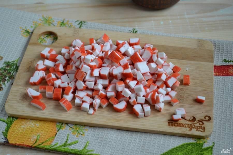 Крабовые палочки разморозьте и порежьте мелкими кубиками.
