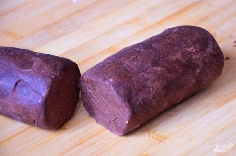 Вбиваем в смесь желток, добавляем сметану и перемешиваем. Из влажной плотной массы формируем колбаску, делим ее на пару частей: большую и чуть поменьше. Убираем тесто в холодильник на полчаса.