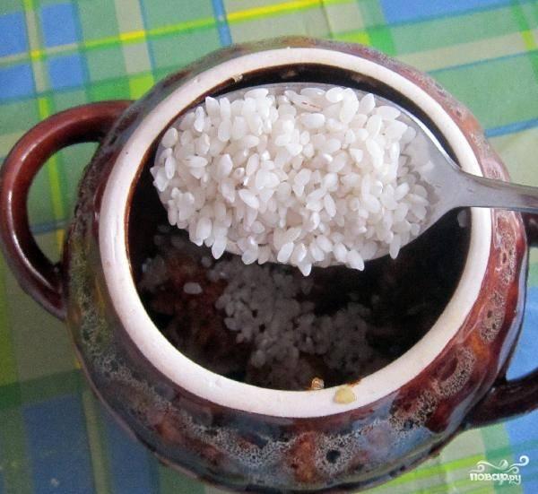 Рис предварительно промываем и засыпаем по 2 столовые ложки в каждый горшочек и заливаем водой так, чтобы жидкость была выше риса на 1-1,5 сантиметра.