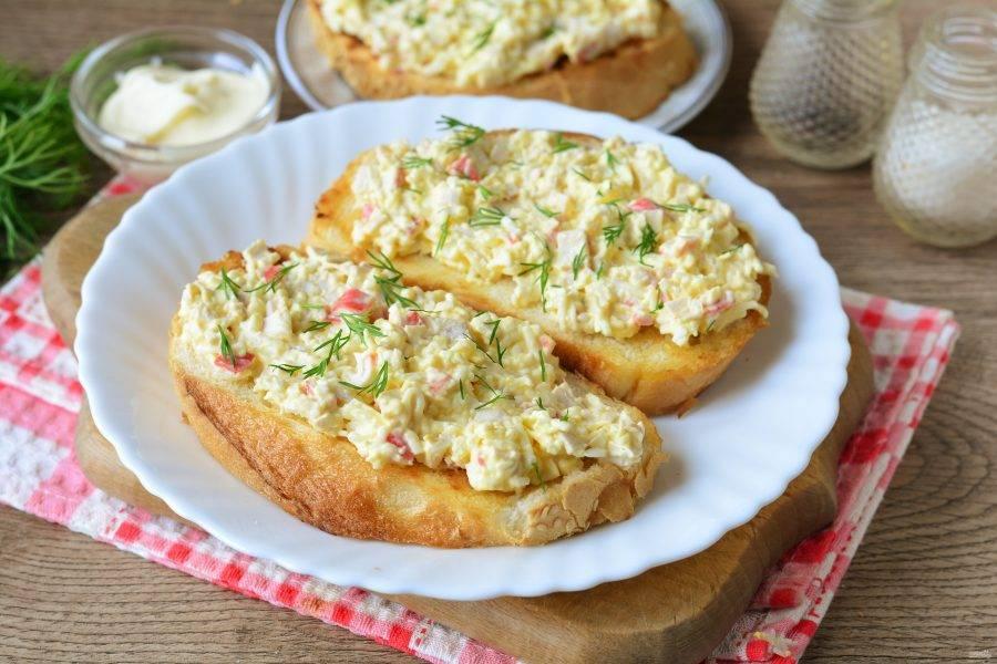 Смажьте бутерброды крабовой начинкой, присыпьте для декора мелко рубленой зеленью.