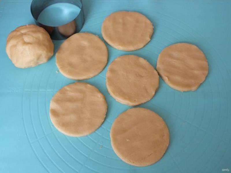 Включите духовку на 180 градусов. По истечении времени, раскатайте тесто в пласт толщиной 0,5-1 см. Круглой вырубкой нарежьте песочники.