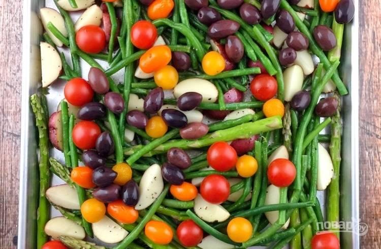 2.Выложите содержимое миски на противень, добавьте поверх оливки, томаты, полейте салат оливковым маслом, посолите и поперчите, перемешайте. Отправьте противень на 20 минут в разогретый до 200 градусов духовой шкаф.