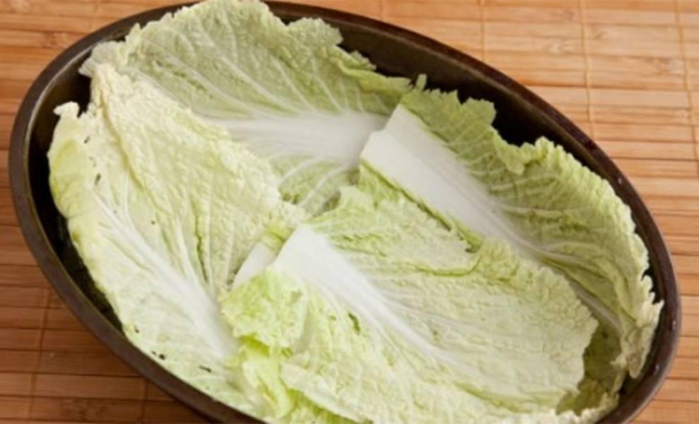 7. Утятницу смажьте растительным маслом. На дно выложите пару листов пекинской капусты.