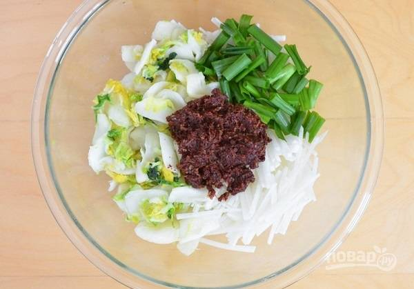 6. В глубокую мисочку отправьте капусту, немного нарезанного тонкими брусочками дайкона и зеленый лук. Выложите пасту из специй.