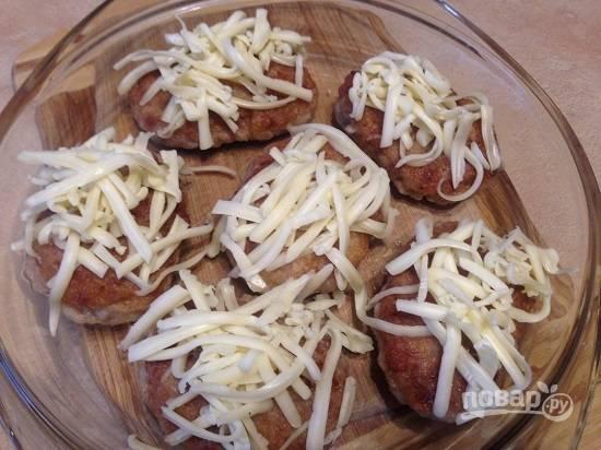 Посыпаем практически готовые котлеты сыром.