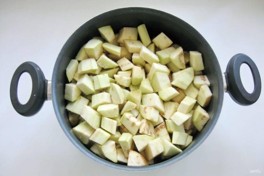 Выложите нарезанные баклажаны в кастрюлю. Посыпьте двумя чайными ложками соли и перемешайте. Дайте постоять 20 минут. После слейте образовавшуюся жидкость.