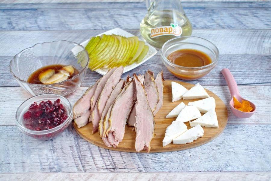 Запеченное мясо немного остудите, нарежьте на тонкие ломтики. Грушу разрежьте пополам, удалите семенную коробочку, также нарежьте на тонкие ломтики. Сыр нарежьте на треугольные ломтики, орехи измельчите.