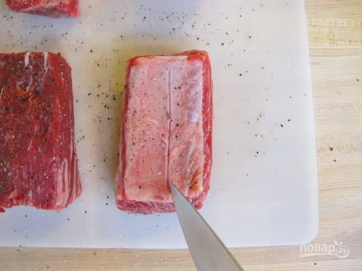 1. Рёбрышки смажьте солью и перцем. Посередине, со стороны кожицы, на каждом кусочке сделайте надрез ножом.