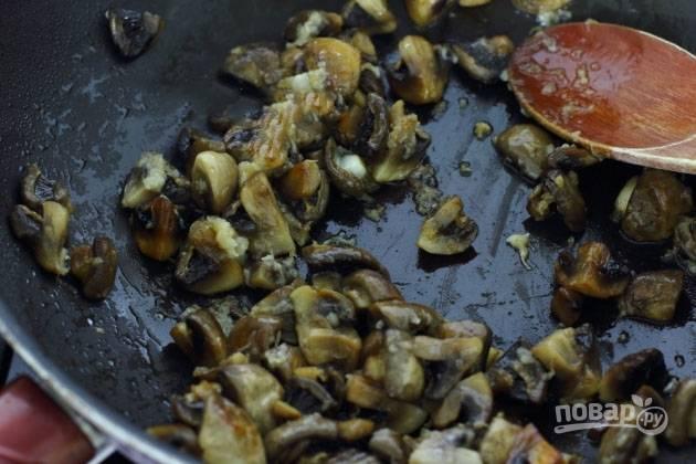 Добавляем к грибам измельченный чеснок и обжариваем еще примерно минуту.