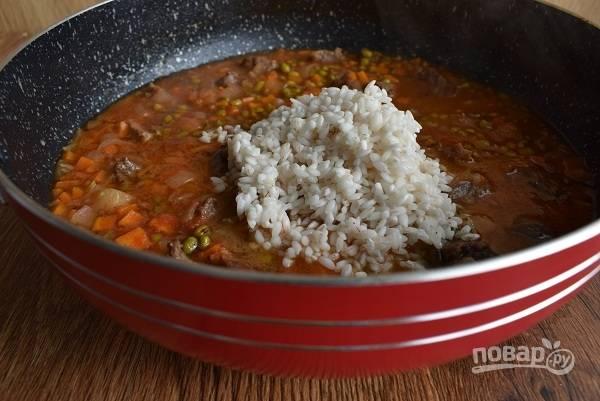 Добавьте рис, варите до готовности. Посолите и поперчите по вкусу.