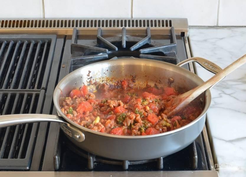 5. После этого добавьте перетёртые помидоры и 0,25 ч. ложки соли. Готовьте ингредиенты вместе ещё 5 минут, иногда помешивая.