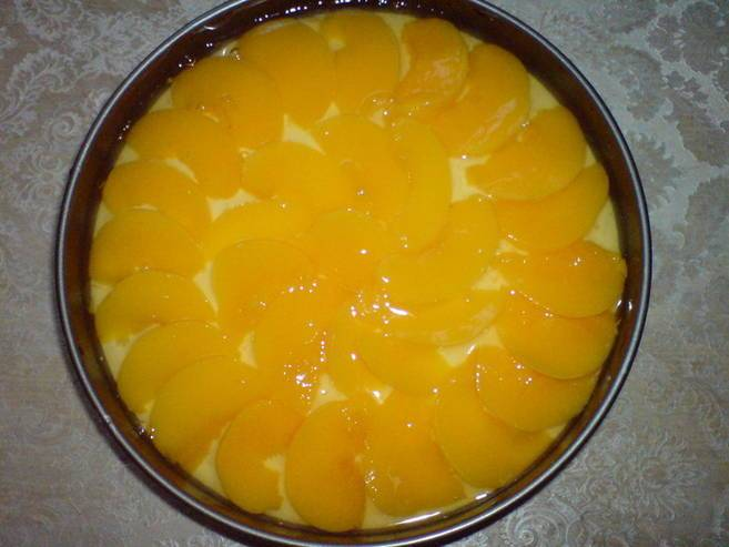 На дно формы выложить яблоки, залить тестом и выложить персики, слегка вдавливая в тесто.