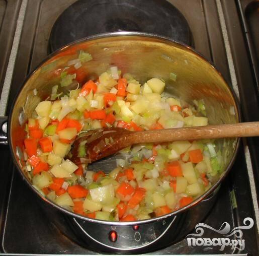 2.В большую глубокую кастрюлю налить подсолнечного масла. Когда масло нагреется добавить порей, картофель и морковь и пассировать 5-6 минут, часто помешивая.