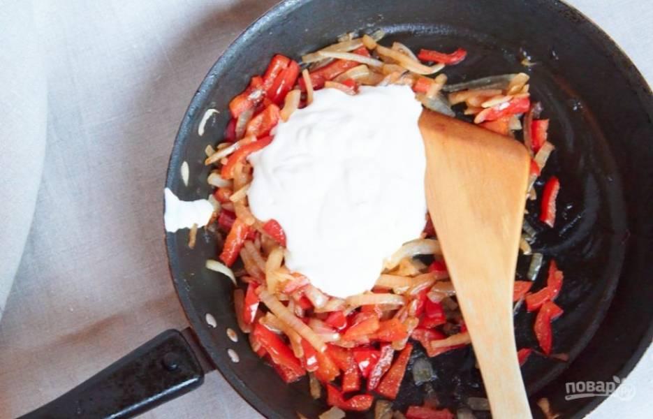 Сбавляем огонь почти до минимума, возвращаем в сковороду курицу, добавляем сметану, перемешиваем и тушим около 5 минут.