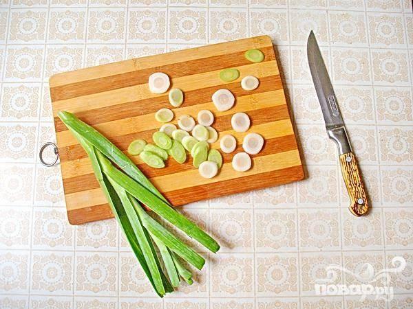 1. В  приготовлении блюда мы используем парж, он более нежный репчатого лука, и намного пикантнее порея. Промываем парж и нарезаем его колечками, и зелень, и белую часть. Горшочки смазываем растительным маслом, и на их дно укладываем парж.
