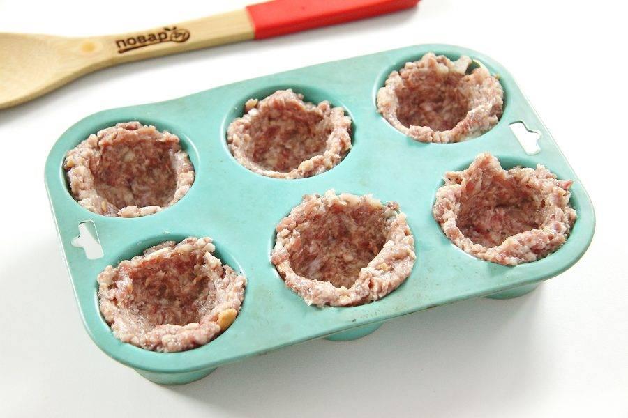 В формочки для кексов положите немного фарша и сделайте в нем углубление, формируя стенки.