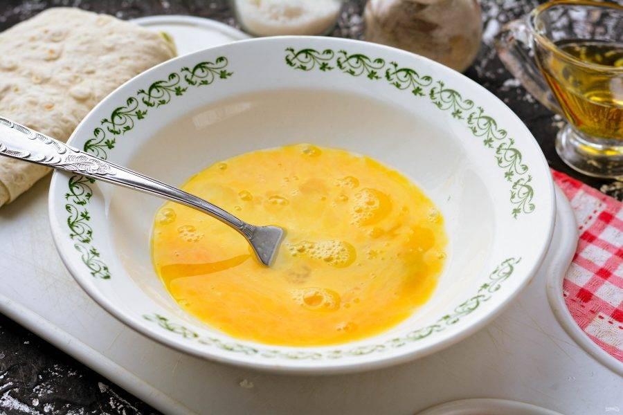 Вбейте яйца в миску и добавьте по вкусу соль и перец. Взболтайте кляр вилочкой.