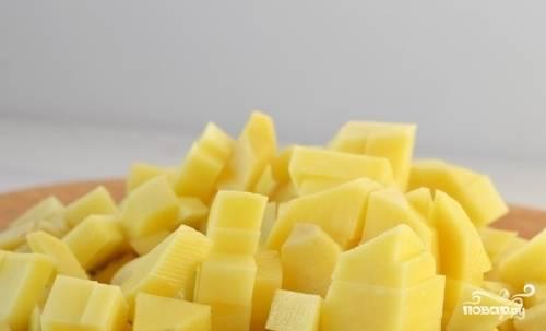 Вскипятите 1,5 литра воды. Картофель помойте, почистите и нарежьте кубиками.