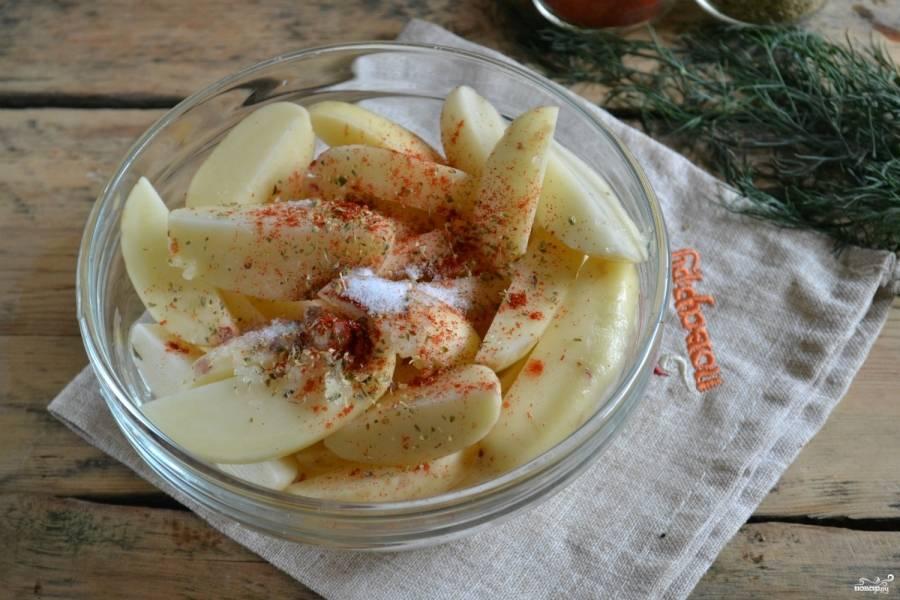 Картофель посолите, сбрызните подсолнечным маслом и посыпьте специями, хорошенько перемешайте, чтобы приправы равномерно распределились по всем кусочкам.