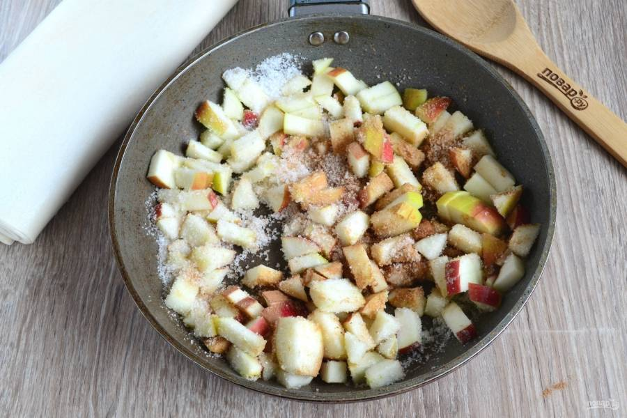 Переложите яблоки в сковороду с разогретым сливочным маслом, засыпьте сахаром и корицей. Тушите на медленном огне 5-7 минут.