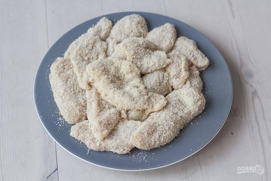 Затем каждый кусочек курицы обваляйте в муке, потом в яйце и, наконец, в смеси сухарей и сыра.